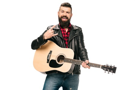 handsome smiling musician in black leather jacket holding acoustic guitar and showing rock and roll sign, isolated on white Stockfoto