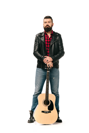 handsome rocker in black leather jacket posing with acoustic guitar, isolated on white