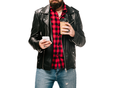 cropped view of man in black leather jacket holding coffee to go and using smartphone, isolated on white