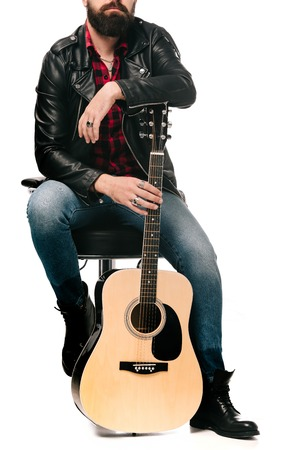 cropped view of musician in black leather jacket posing with acoustic guitar, isolated on white