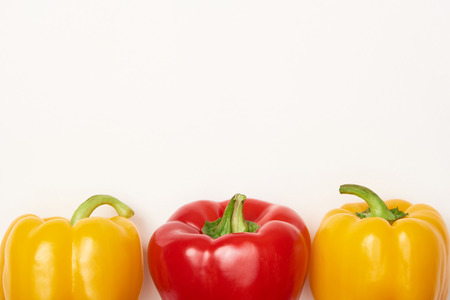 Studio shot of red and yellow bell peppers on white background