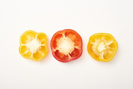 Studio shot of cut yellow and red bell peppers on white background