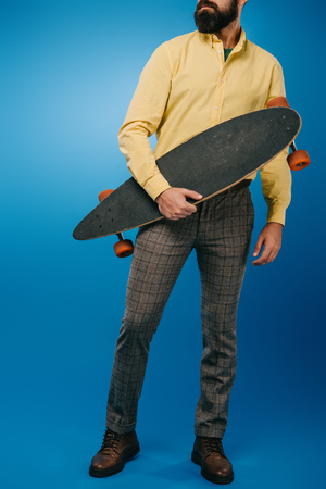 cropped view of man holding skateboard isolated on blue 写真素材