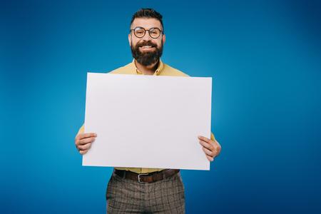 fröhlicher Mann mit leerem Plakat isoliert auf blau Standard-Bild