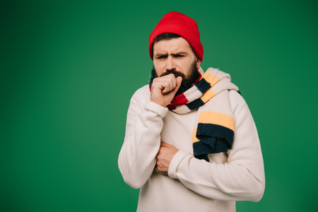 ill man in hat and scarf coughing isolated on green