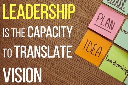 top view of paper stickers with words plan, idea and leadership on wooden tabletop with Leadership is the capacity to translate vision lettering