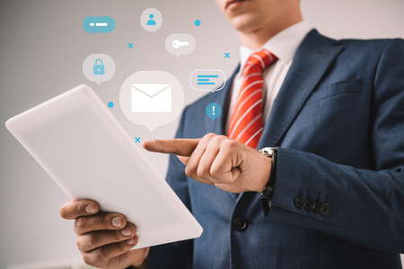 cropped view of businessman using digital tablet with marketing strategy icons