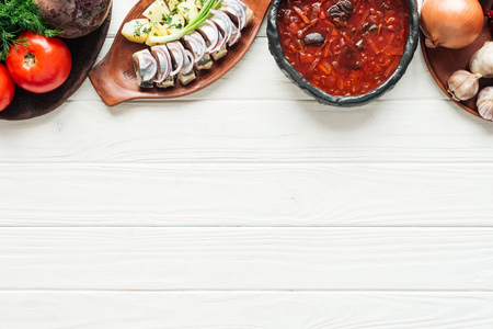 traditional beetroot soup, herring and ingredients on white wooden background with copy space