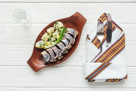 marinated herring, potatoes and onions in earthenware plate with glass of vodka, cutlery and embroidered towel on white wooden background Standard-Bild - 116519410