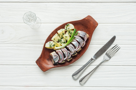 top view of marinated herring, potatoes and onions in earthenware plate with glass of vodka and cutlery on white wooden background Reklamní fotografie