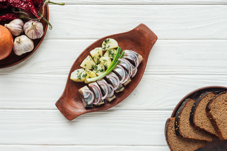 top view of marinated herring with potatoes and onions in earthenware plate with rye bread on white wooden background Stock fotó