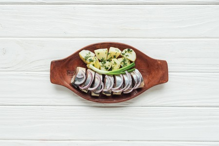 top view of marinated herring with potatoes and onions in earthenware plate on white wooden background