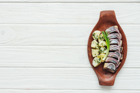 delicious marinated herring with potatoes and onions in earthenware plate on white wooden background with copy space Imagens