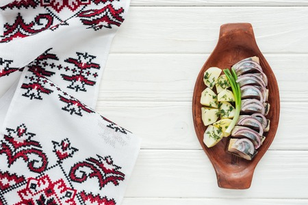 top view of marinated herring with potatoes and onions in earthenware plate with embroidered towel on white wooden background