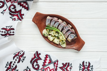 traditional marinated herring with potatoes and onions in earthenware plate with embroidered towel on white wooden background Standard-Bild - 116519422