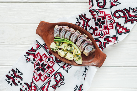 traditional marinated herring with potatoes and onions in earthenware plate with embroidered towel on white wooden background Stock fotó