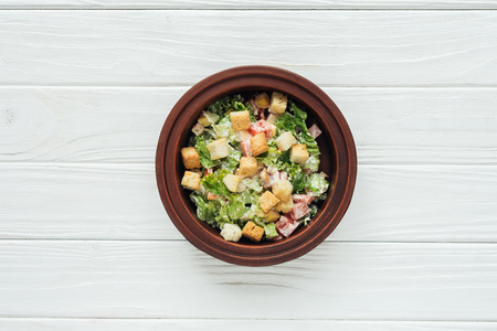 top view of tasty caesar salad with croutons in bowl on white wooden background