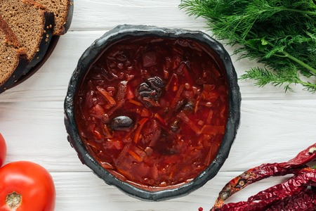 bowl of traditional beetroot soup with ingredients on white wooden background