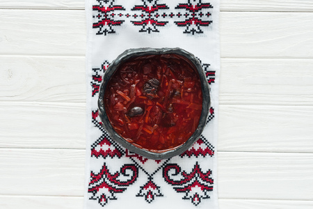 bowl of tasty traditional beetroot soup with embroidered towel on white wooden background Standard-Bild - 116549330