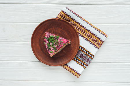 top view of tasty traditional russian salad on plate with embroidered towel on white wooden background Standard-Bild - 116549334
