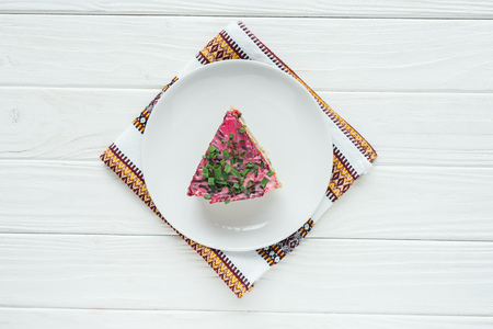 top view of delicious traditional russian salad on plate with embroidered towel on white wooden background Stockfoto