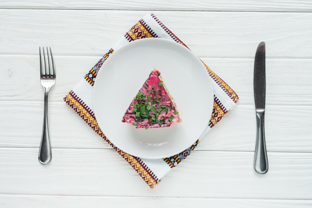 top view of delicious traditional russian salad on plate with embroidered towel and cutlery on white wooden background Stockfoto