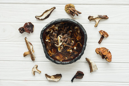 top view of tasty traditional mushroom soup with circle of dried mushrooms on white wooden background