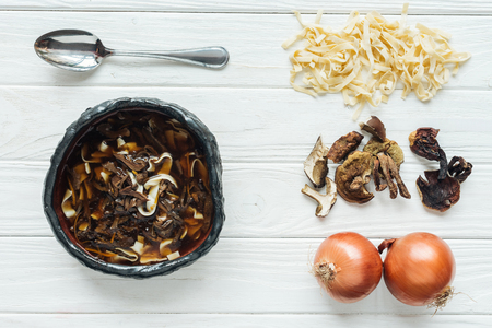 top view of traditional mushroom soup with spoon and ingredients on white wooden background