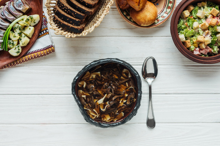 top view of tasty traditional mushroom soup, spoon and dishes around on white wooden background Stock fotó