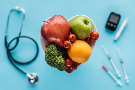 selective focus of fruits and vegetables in heart shaped bowl with medical equipment on blue background Zdjęcie Seryjne - 116564385