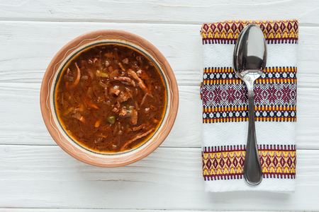 top view of delicious traditional mixed meat soup with spoon and embroidered towel on white wooden background Standard-Bild - 116564391