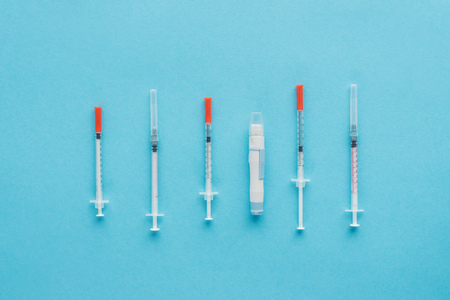 top view of insulin syringes for diabetes on blue background