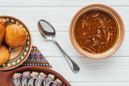 Draufsicht auf leckere traditionelle gemischte Fleischsuppe mit Mini-Kuchen und Löffel auf weißem Holzhintergrund