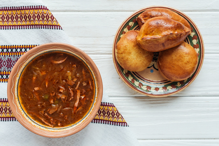 delicious traditional mixed meat soup with mini pies and embroidered towel on white wooden background Standard-Bild - 116556282