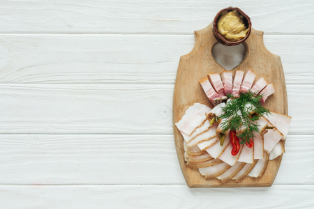 top view of traditional sliced smoked lard with mustard on cutting board with white wooden background and copy space