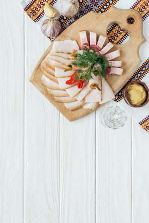 traditional sliced smoked lard on cutting board with mustard, embroidered towel and glass of vodka on white wooden background Standard-Bild - 116556152