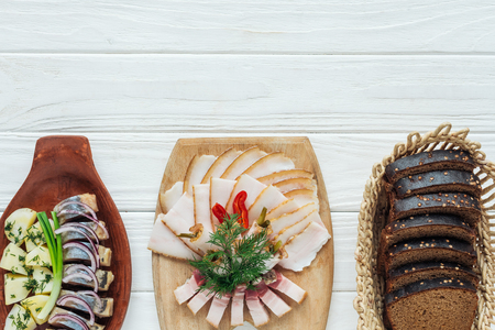 traditional sliced smoked lard on cutting board, rye bread and herring on white wooden background