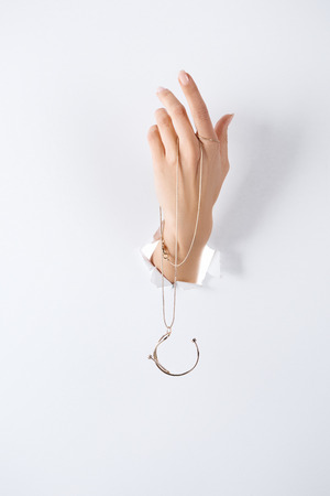 cropped image of woman holding hand with beautiful luxury necklace through white paper 免版税图像