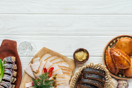 top view of traditional sliced smoked lard on cutting board, rye bread, herring and mini pies on white wooden background