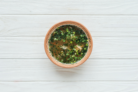 top view of tasty traditional fish soup with green onion on white wooden background Banco de Imagens