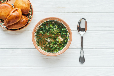 top view of traditional fish soup with green onion, spoon and mini pies on white wooden background