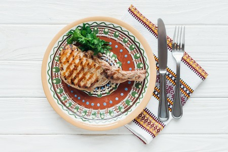 delicious rib eye meat steak on plate with parsley, cutlery and embroidered towel on white wooden background