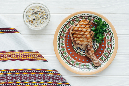 tasty rib eye meat steak on plate with parsley, sauce and embroidered towel on white wooden background