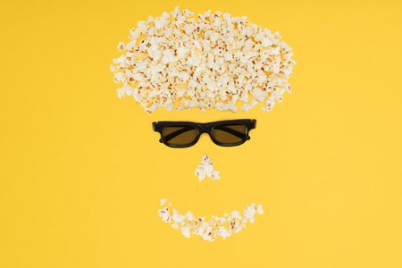 stereoscopic 3d glasses and fresh popcorn isolated on yellow