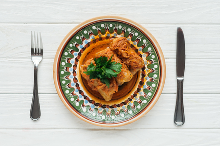 top view of tasty stuffed cabbage rolls with parsley on plate, cutlery and white wooden background