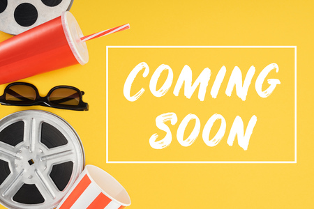 film reels, 3d glasses, popcorn bucket, red disposable cup with straw and coming soon lettering isolated on yellow