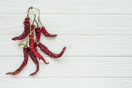 top view of bundle of red chilli peppers on white wooden background with copy space