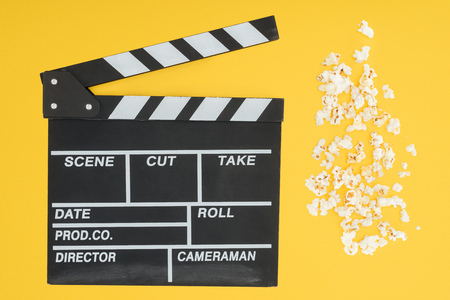 top view of clapperboard and fresh crunchy popcorn isolated on yellow Banco de Imagens