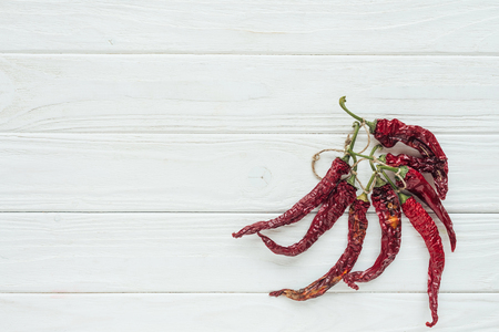 bundle of red chilli peppers on white wooden background with copy space 스톡 콘텐츠
