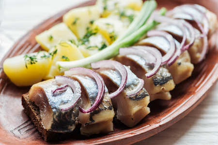 close up of tasty marinated herring with potatoes and onions in earthenware plate Stok Fotoğraf